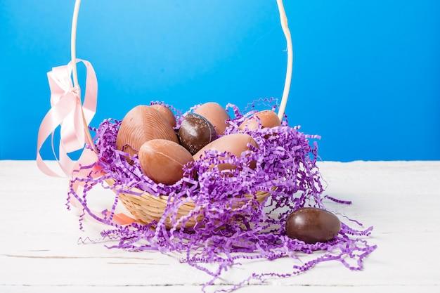 Kurczak, jajka czekoladowe, fioletowy papier dekoracyjny w koszyku