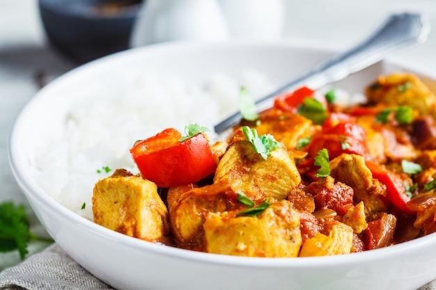 Kurczak jalfrezi z ryżem w białej misce. koncepcja tradycyjnej kuchni indyjskiej.