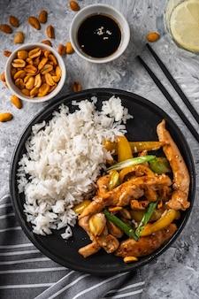Kurczak kung pao, smażone chińskie tradycyjne syczuańskie danie z kurczakiem, orzeszkami ziemnymi, warzywami i papryką chili.
