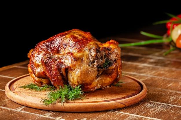 Kurczak leży na drewnianej desce.