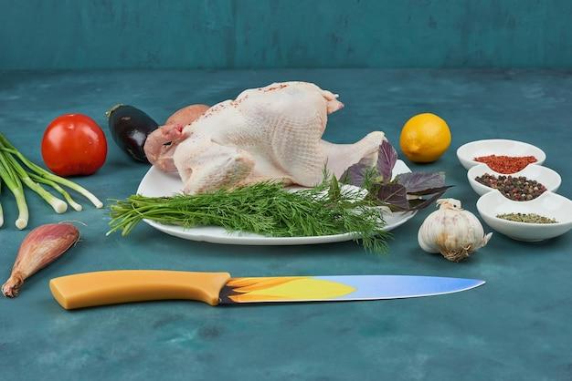 Kurczak na białym talerzu z ziołami i przyprawami.