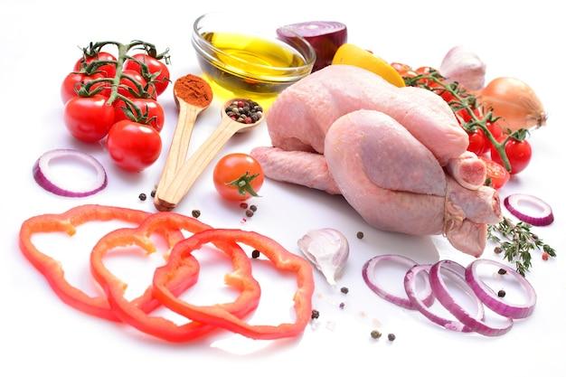 Kurczak na białym tle z przyprawami i warzywami