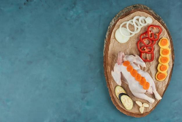 Kurczak na drewnianym talerzu z warzywami.