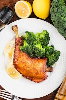 Kurczak nogi z warzywami na drewnianym stole.