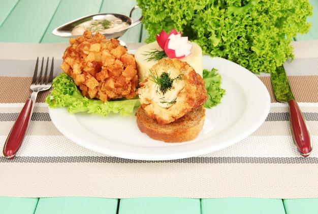 Kurczak po kijowie z puree ziemniaczanym na białym talerzu, na drewnianym tle