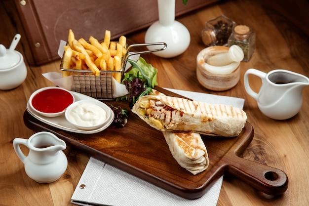 Kurczak shawarmin pitw z frytkami keczup majonezem i sałatą na stole