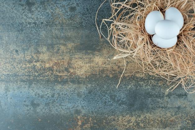 Kurczak świeżych białych jaj leżących w sianie na tle marmuru