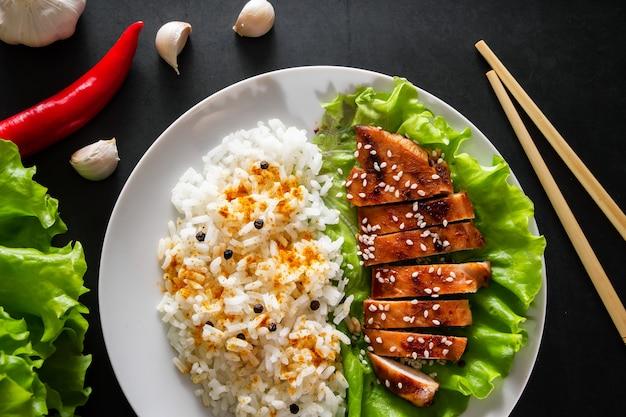Kurczak teriyaki z białym ryżem na talerzu. smaczne jedzenie i chińskie paluszki na ciemnym tle