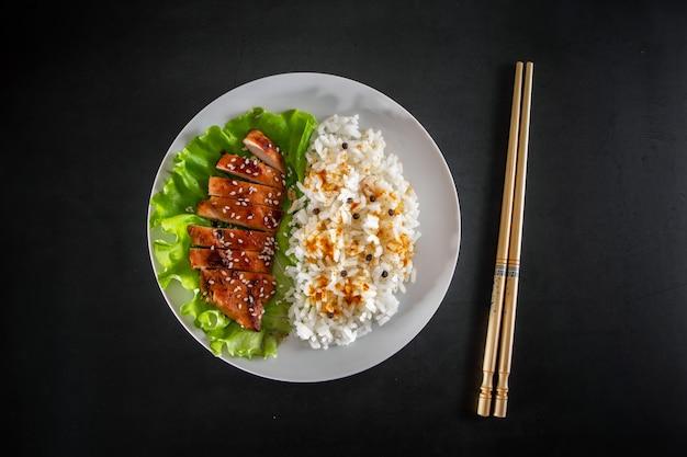 Kurczak teriyaki z białym ryżem na talerzu