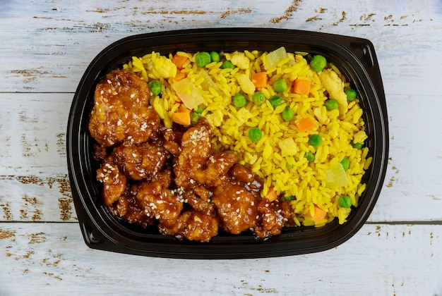Kurczak teriyaki z ryżem i warzywami w plastikowym pojemniku na żywność. kuchnia japońska. widok z góry.