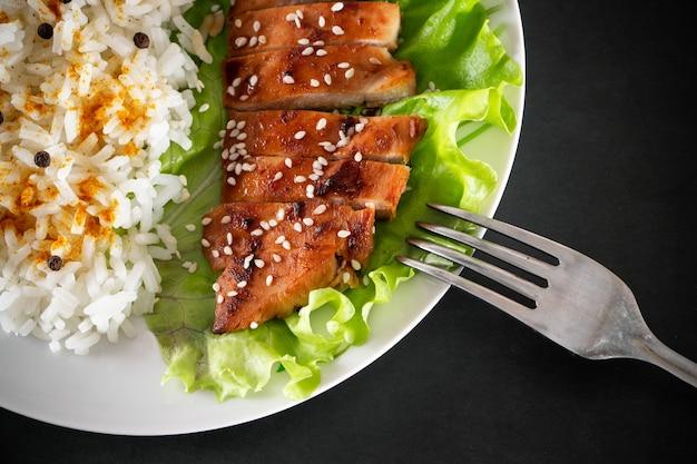 Kurczak teriyaki z sałatą sezamową i ryżem na białym talerzu danie z widelcem
