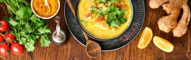 Kurczak tikka masala. tradycyjne indyjskie curry i składniki na ciemnym tle. curry, limonka, imbir, kolendra, chili, ryż, zioła i przyprawy. widok z góry. transparent.