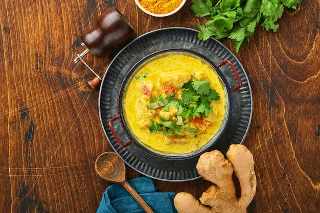 Kurczak tikka masala. tradycyjne indyjskie curry i składniki na ciemnym tle. curry, limonka, imbir, kolendra, chili, ryż, zioła i przyprawy. widok z góry z miejsca na kopię.