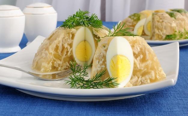 Kurczak w galarecie ozdobiony jajkiem i koperkiem