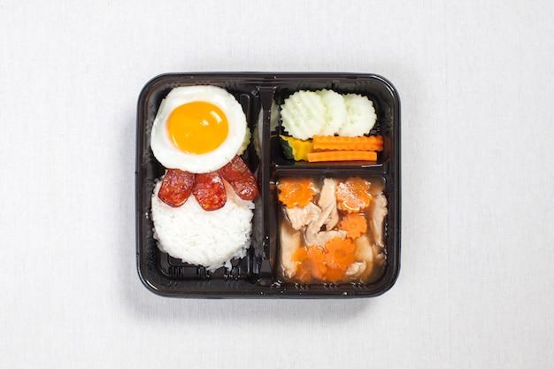 Kurczak w sosie z jajkiem sadzonym na ryżu w czarnym plastikowym pudełku, na białym obrusie, pudełko na żywność, tajskie jedzenie.