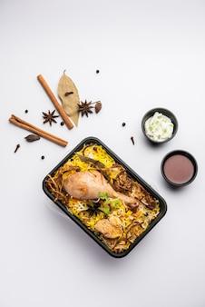 Kurczak w stylu restauracyjnym tikka biryani pakowany do dostawy do domu w plastikowym pudełku lub pojemniku z raitą i salan