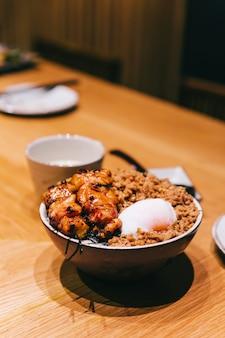 Kurczak yakitori rice bowl z mieloną wieprzowiną podawany z chińskim jajkiem na parze, łyżką i pałeczkami.
