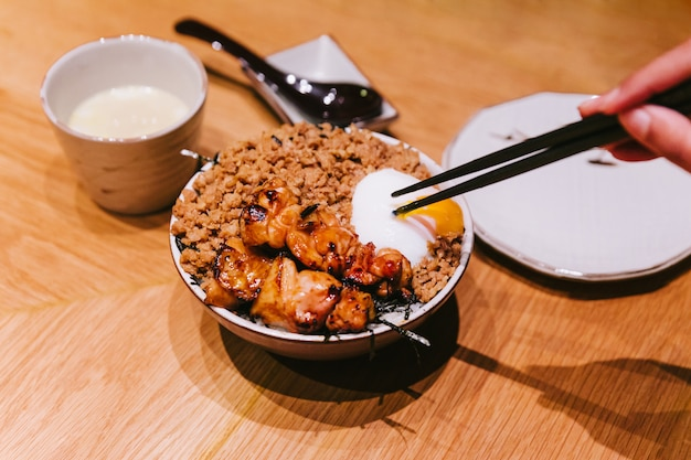 Kurczak yakitori rice bowl z mieloną wieprzowiną podawany z chińskim jajkiem na parze
