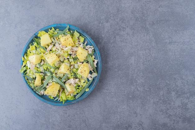 Kurczak z gotowanymi ziemniakami na niebieskim talerzu.