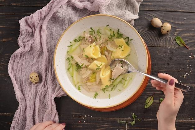 Kurczak z mięsem, warzywami i zieloną cebulą. w białym talerzu na drewnianym stole
