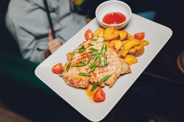 Kurczak z pieczonymi ziemniakami na białym talerzu.