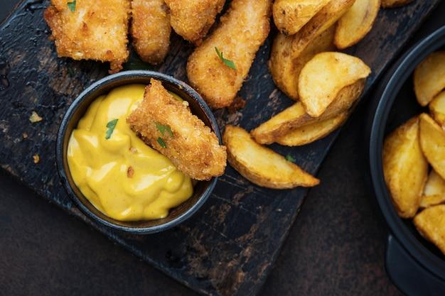 Kurczak z sosem i ziemniakami na ciemnym stole widok z góry