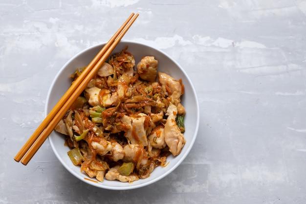 Kurczak z warzywami w białej misce na ceramicznym tle