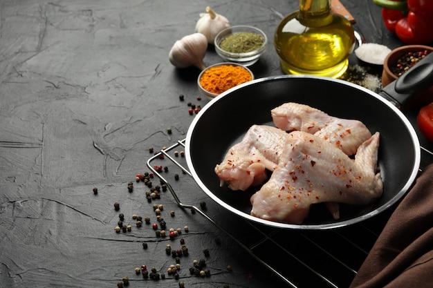 Kurczaka surowy mięso i pikantność na czerni, przestrzeń dla teksta