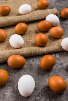 Kurczaków jajka rozpraszający na kanwie na popielatym stole
