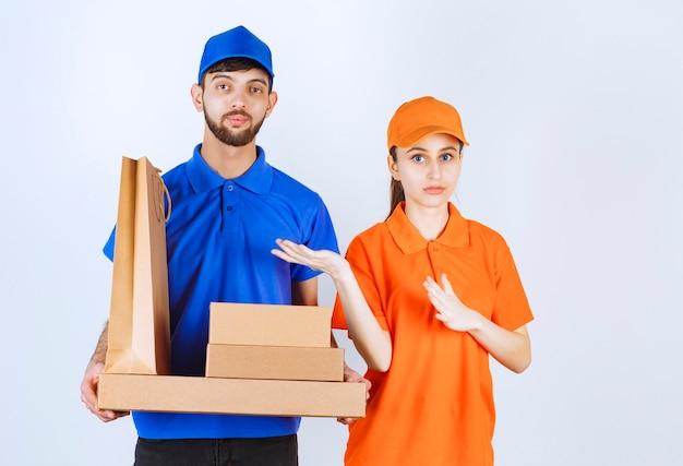 Kurier chłopiec i dziewczynka w niebiesko-żółtych mundurach, trzymając kartonowe pudełka na wynos i opakowania na zakupy.
