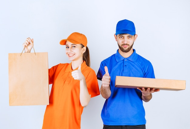 Kurier chłopiec i dziewczynka w niebiesko-żółtych mundurach, trzymając kartonowe pudełka na wynos i paczki na zakupy oraz pokazujący znak dłoni satysfakcji.