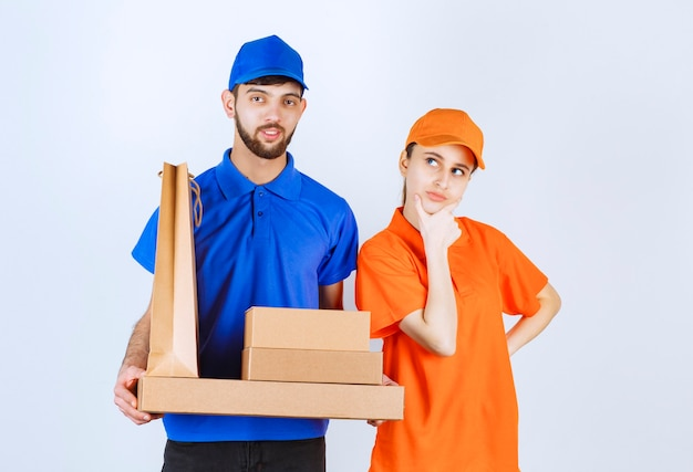 Kurier, chłopiec i dziewczynka w niebiesko-żółtych mundurach, trzymający kartonowe pudełka na wynos i paczki z zakupami, wyglądają na zdezorientowanych i myślą o nowych pomysłach.
