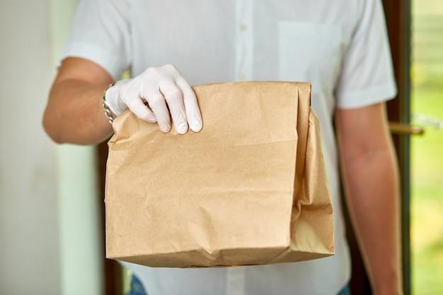 Kurier, człowiek dostawy w lateksowych rękawiczkach medycznych bezpiecznie dostarcza zakupy online w brązowych papierowych torbach do drzwi podczas epidemii koronawirusa