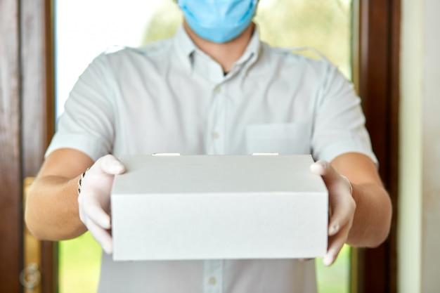 Kurier, człowiek dostawy w lateksowych rękawiczkach medycznych i masce bezpiecznie dostarcza zakupy online w białym pudełku do drzwi podczas epidemii koronawirusa