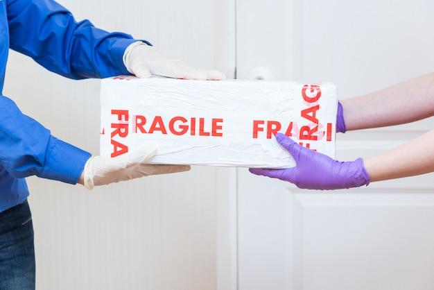 Kurier dostarcza delikatną paczkę do drzwi w lateksowych rękawiczkach, bezdotykowo w okresie kwarantanny