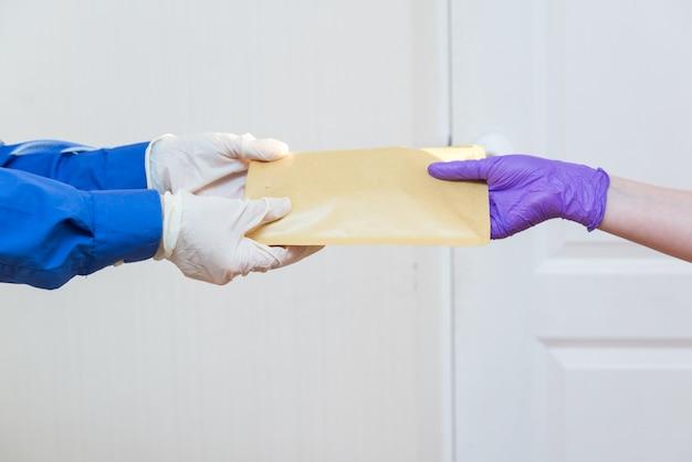 Kurier dostarcza paczkę do drzwi w lateksowych rękawiczkach, bezdotykowo, w okresie kwarantanny