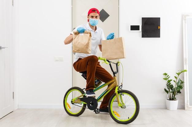 Kurier dostarcza pudełko z jedzeniem podczas pandemii koronawirusa, orientacja pozioma