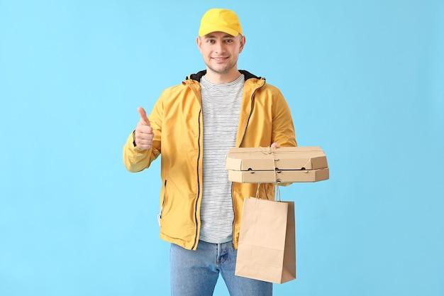 Kurier dostawy jedzenia pokazujący kciuk w górę na kolorowej powierzchni