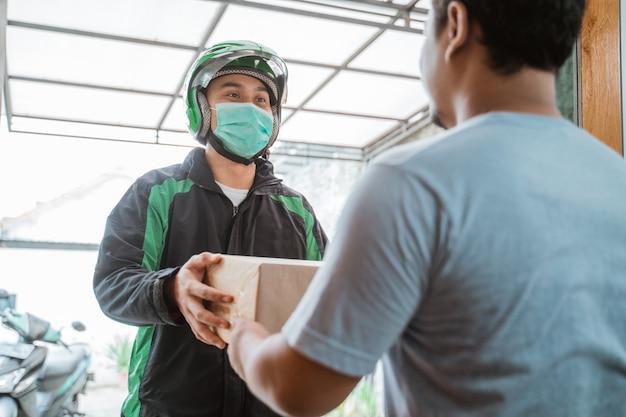 Kurier dostawy w masce na twarz podczas dostarczania paczki