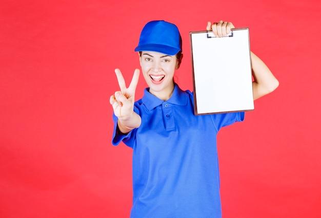Kurier dziewczyna w niebieskim mundurze trzyma listę zadań i pokazuje znak przyjemności.