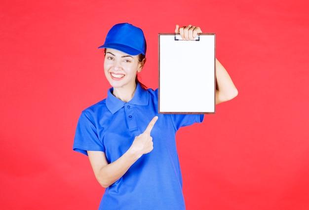 Kurier dziewczyna w niebieskim mundurze trzyma listę zadań.
