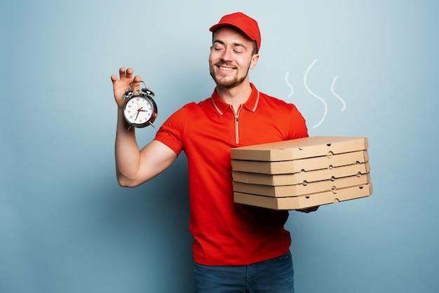 Kurier jest punktualny, aby szybko dostarczać pizze. niebieskie tło