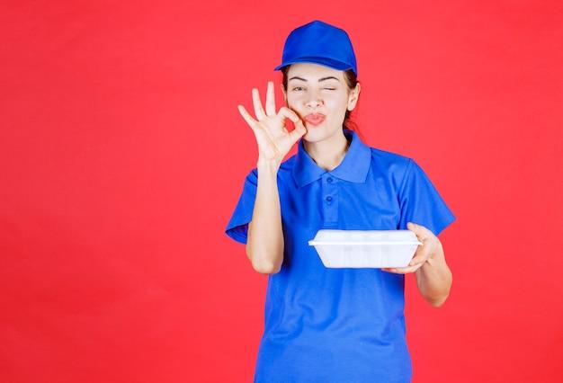 Kurier kobieta w niebieskim mundurze trzymająca listę zadań i pokazująca znak przyjemności.