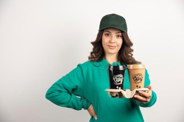 Kurier kobieta w zielonym mundurze trzymając filiżanki kawy.