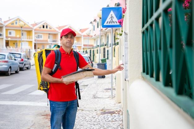 Kurier męski z torbą termiczną, pudełkiem i schowkiem dzwoniącym do drzwi. zamyślony kaukaski doręczyciel lub listonosz stojący na zewnątrz, trzymający paczkę i dostarczający porządek. usługa dostawy i koncepcja poczty