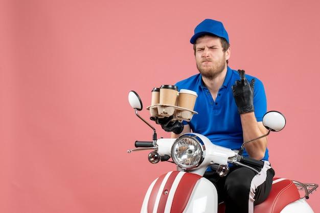 Kurier męski z widokiem z przodu siedzący na rowerze i trzymający filiżanki kawy na różowo