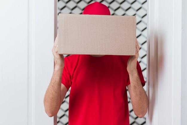 Kurier mężczyzna chuje twarz z pudełkiem