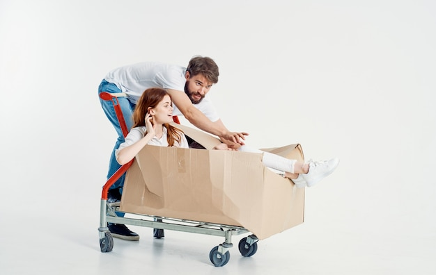 Kurier mężczyzna patrzy na kobietę w pudełku na wózku towarowym