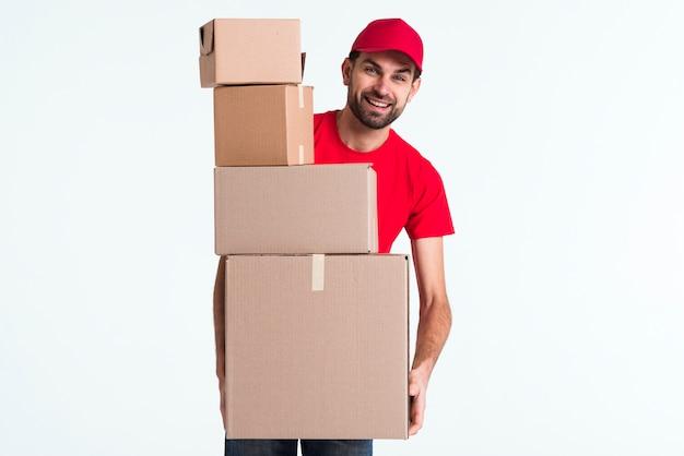 Kurier mężczyzna trzyma stos paczek pocztowych pudełek