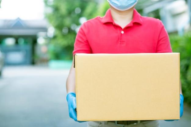 Kurier mężczyzna w czerwonej koszuli rozwozi towary do klientów.
